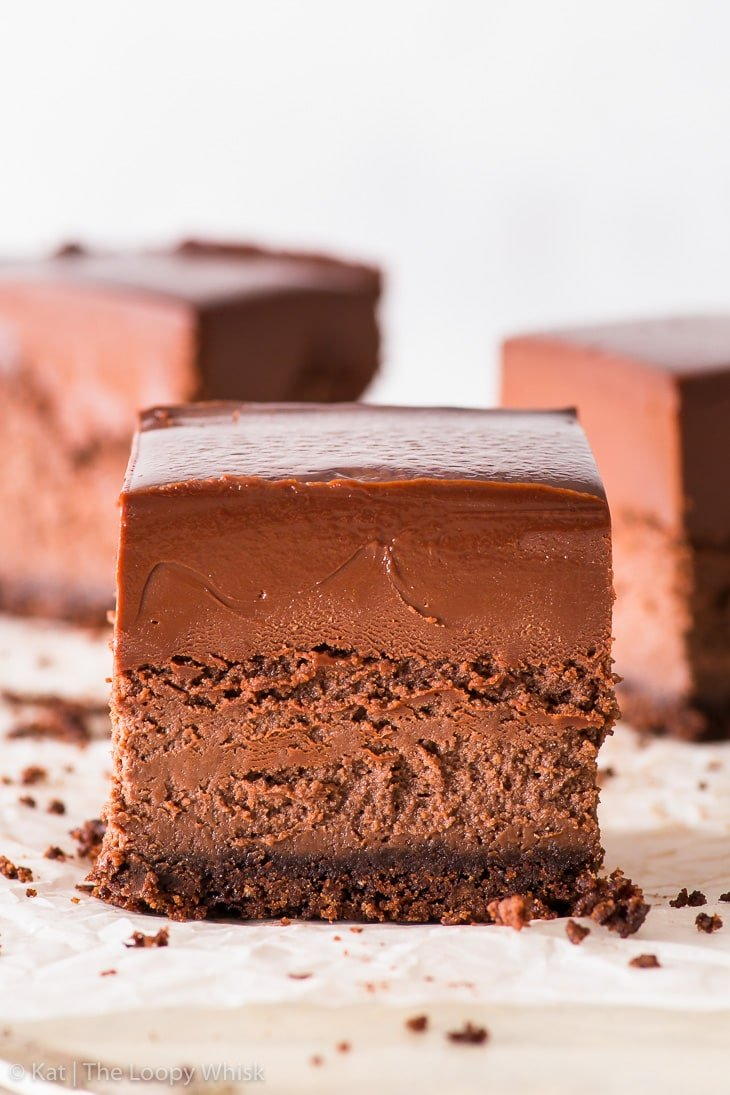 Triple chocolate cheesecake bar on a white backdrop, two more cheesecake bars are in the background.