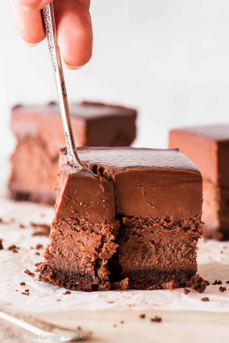 Triple chocolate cheesecake bar on a white backdrop, being eaten with a fork. Two more cheesecake bars are in the background.