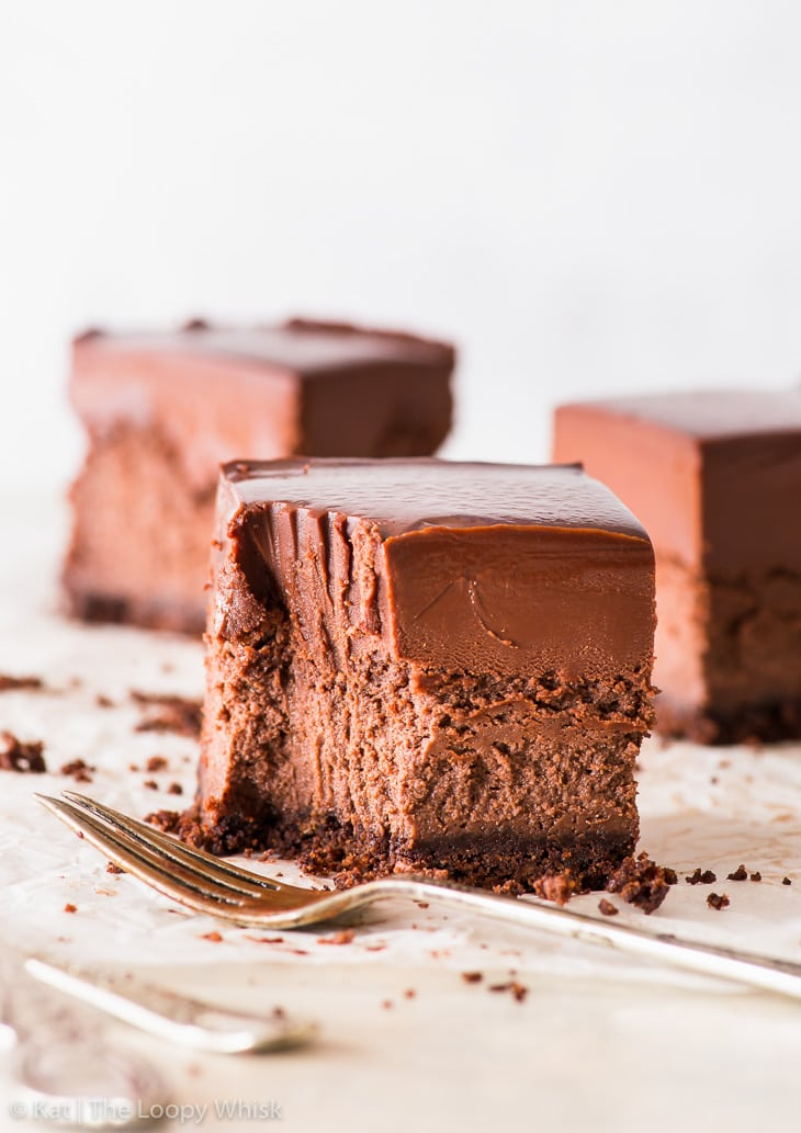 Triple chocolate cheesecake bar on a white backdrop, with a bite having been taken out of it with a fork. Two more cheesecake bars are in the background.