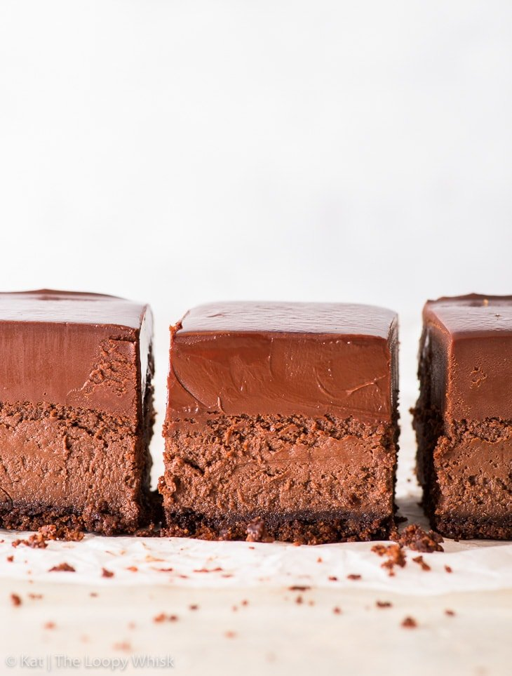 Three chocolate cheesecake bars in a row on a white backdrop.