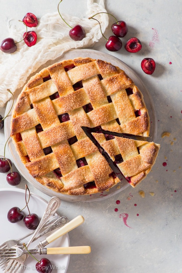 Overhead view of the cherry pie and its regular pie lattice. The pie is surrounded by fresh cherries, plates and forks. A piece of the pie has been cut.