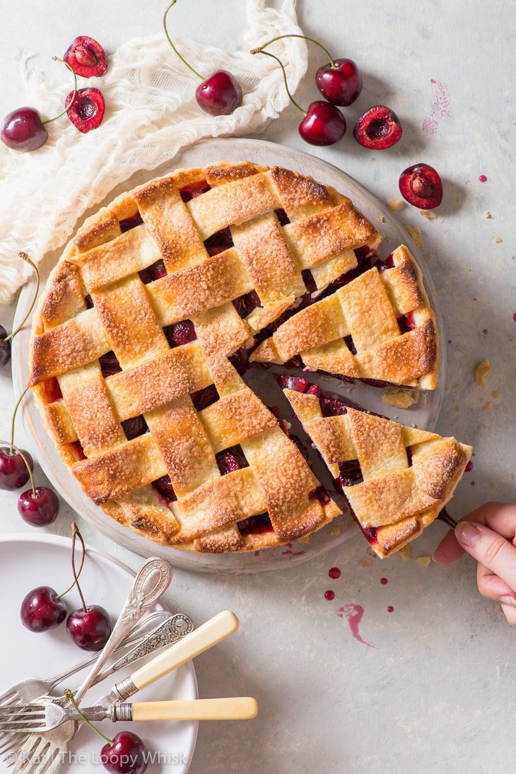 Overhead view of the cherry pie and its regular pie lattice. The pie is surrounded by fresh cherries, plates and forks. Two pieces of the pie has been cut.