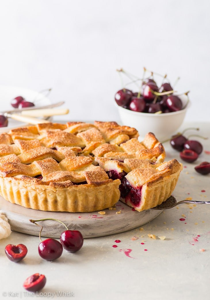 Side view of the cherry pie, with a piece having been cut. A bowl of cherries and plates are in the background.