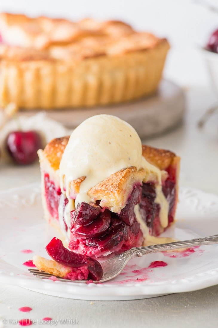 Close-up of a piece of cherry pie served with a scoop of vanilla ice cream on a white dessert plate. The rest of the pie and a bowl of cherries are in the background.