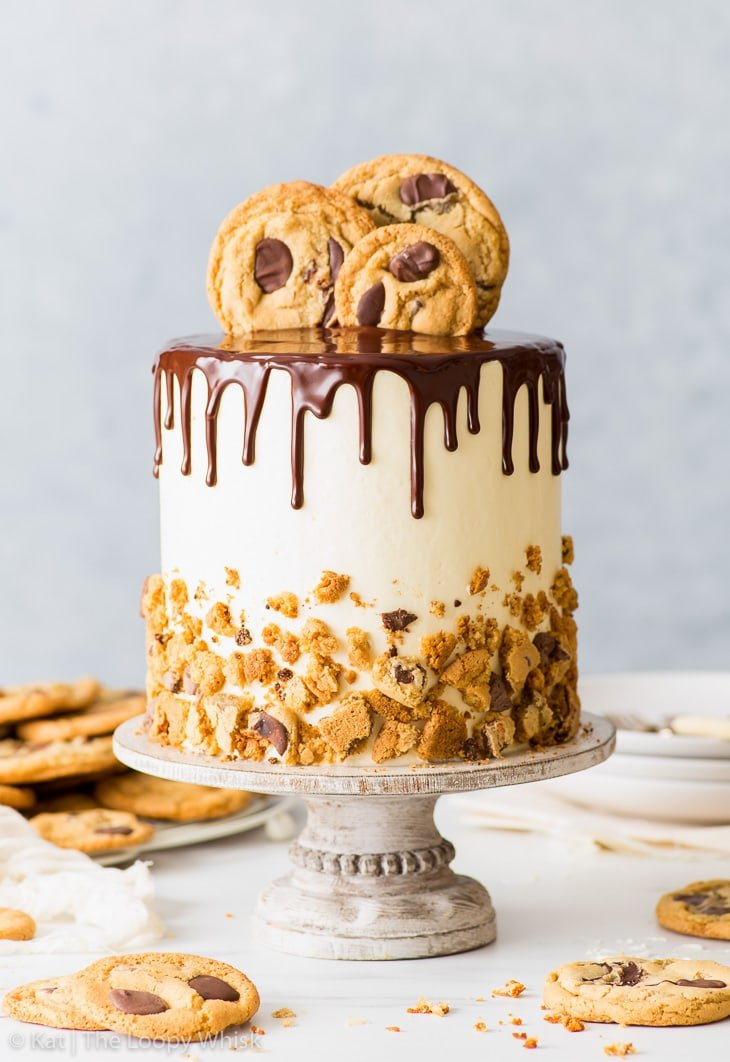 Chocolate chip cookie cake on a white wooden cake stand. More chocolate chip cookies and a few plates are in the background.