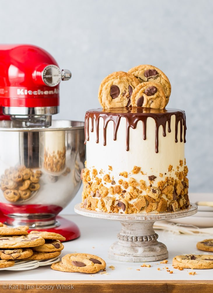 The assembled chocolate chip cookie cake, complete with chocolate chip cookies decorating the top, next to a Queen of Hearts KitchenAid stand mixer.