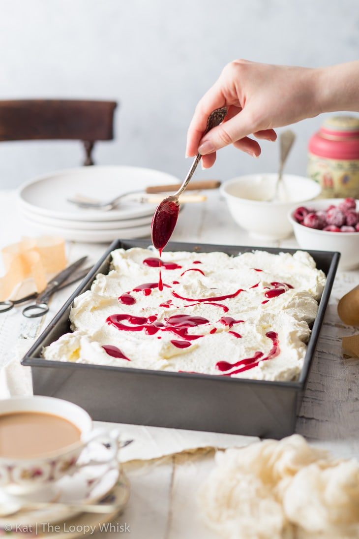Raspberry sheet cake in a metal sheet pan, surrounded by plates and cups on a wooden table. Mascarpone frosting has been spooned onto the cake. Raspberry reduction is being drizzled onto the mascarpone frosting.