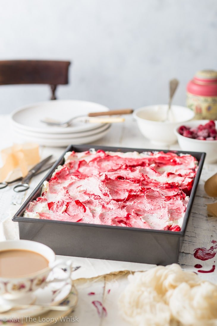 Raspberry sheet cake in a metal sheet pan, surrounded by plates and cups on a wooden table. Mascarpone frosting has been spooned onto the cake.