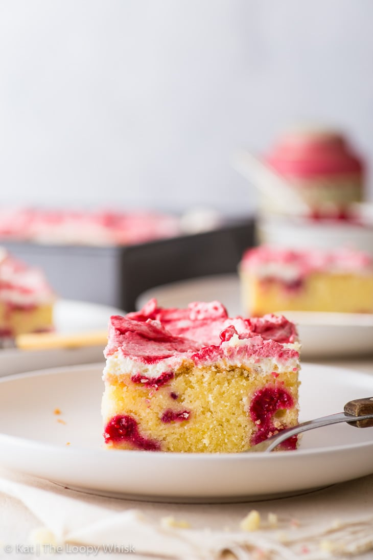 A piece of the raspberry sheet cake on a white plate. The rest of the cake is in the background.