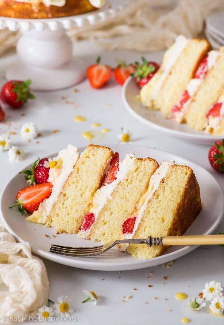 A slice of the strawberry lemonade cake on a white plate. Another slice and the rest of the cake are in the background.