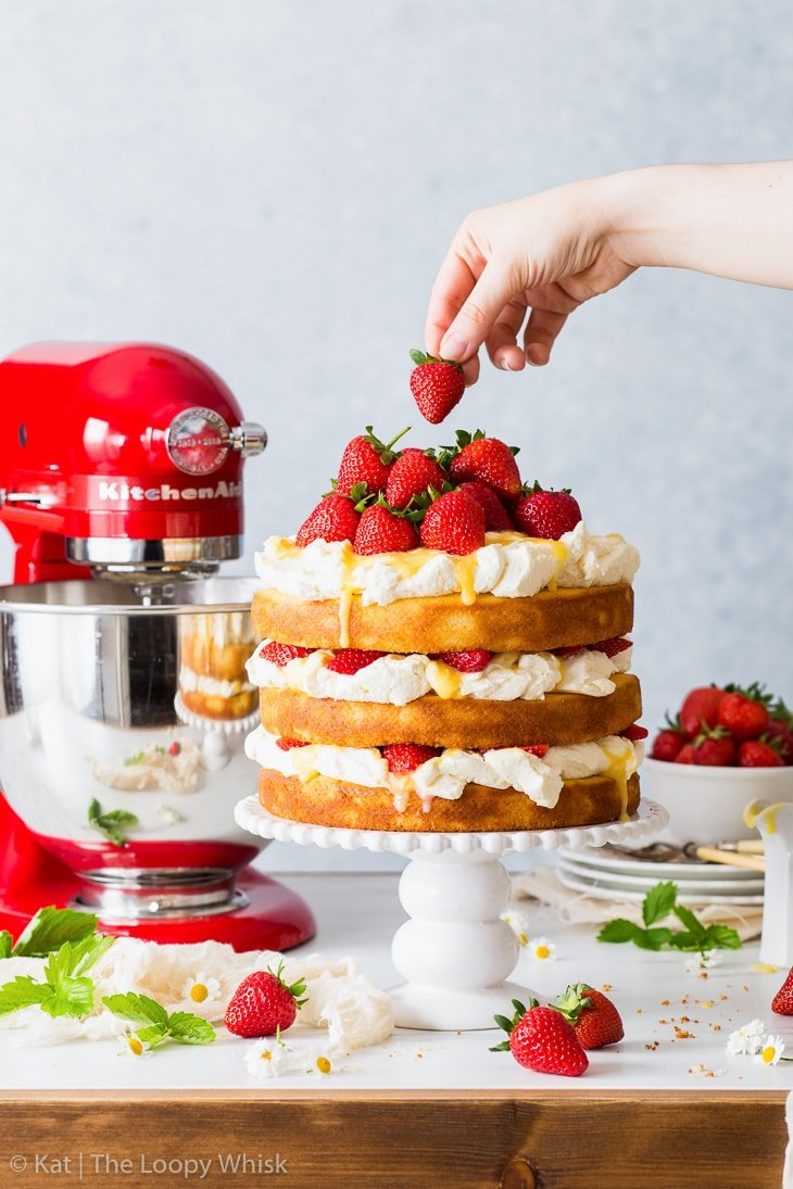 Decorating the top of the strawberry lemonade cake with whole strawberries.