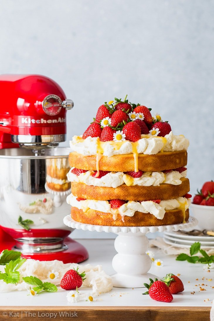 Strawberry lemonade cake on a white cake stand, with a red KitchenAid stand mixer behind it. More strawberries, plates and cutlery is in the background.