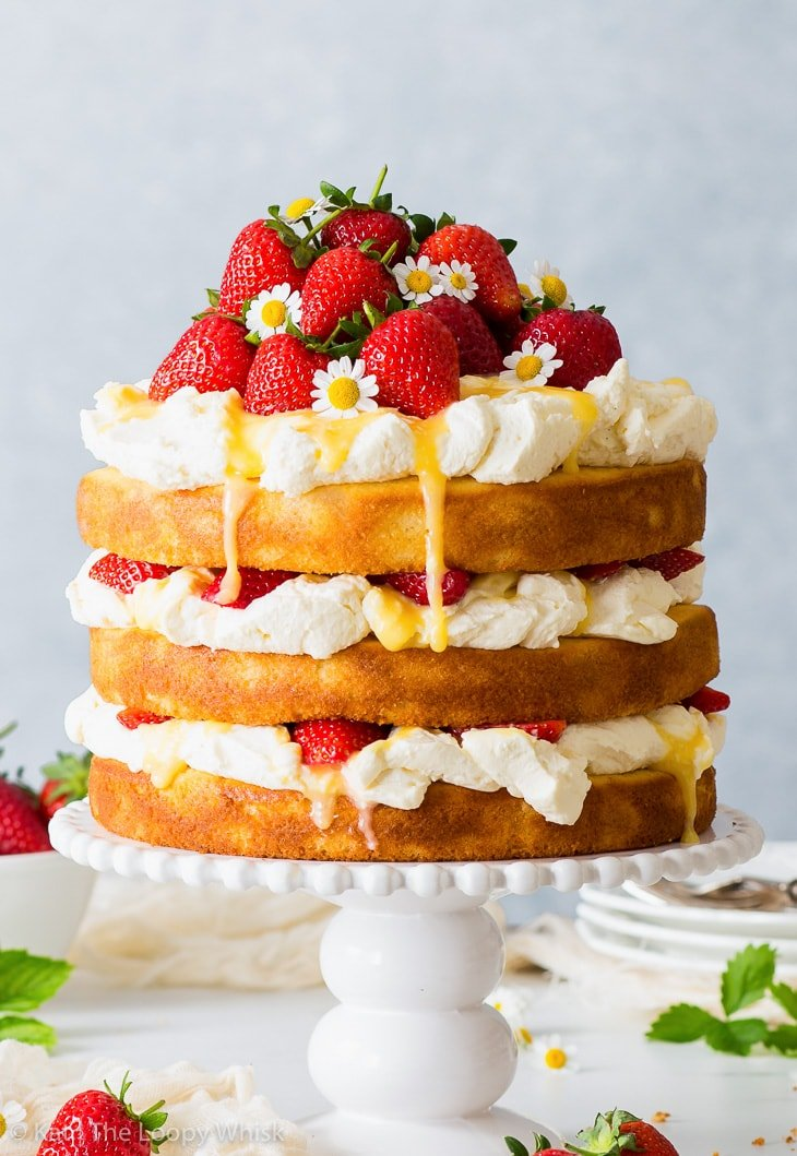 Strawberry lemonade cake on a white cake stand. A bowl of fresh strawberries, plates and cutlery are in the background.