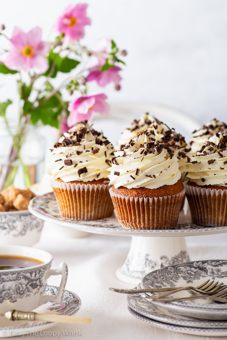 Banoffee pie cupcakes on a cake stand, with flowers in the background. A cup of tea and dessert plates are in the foreground.