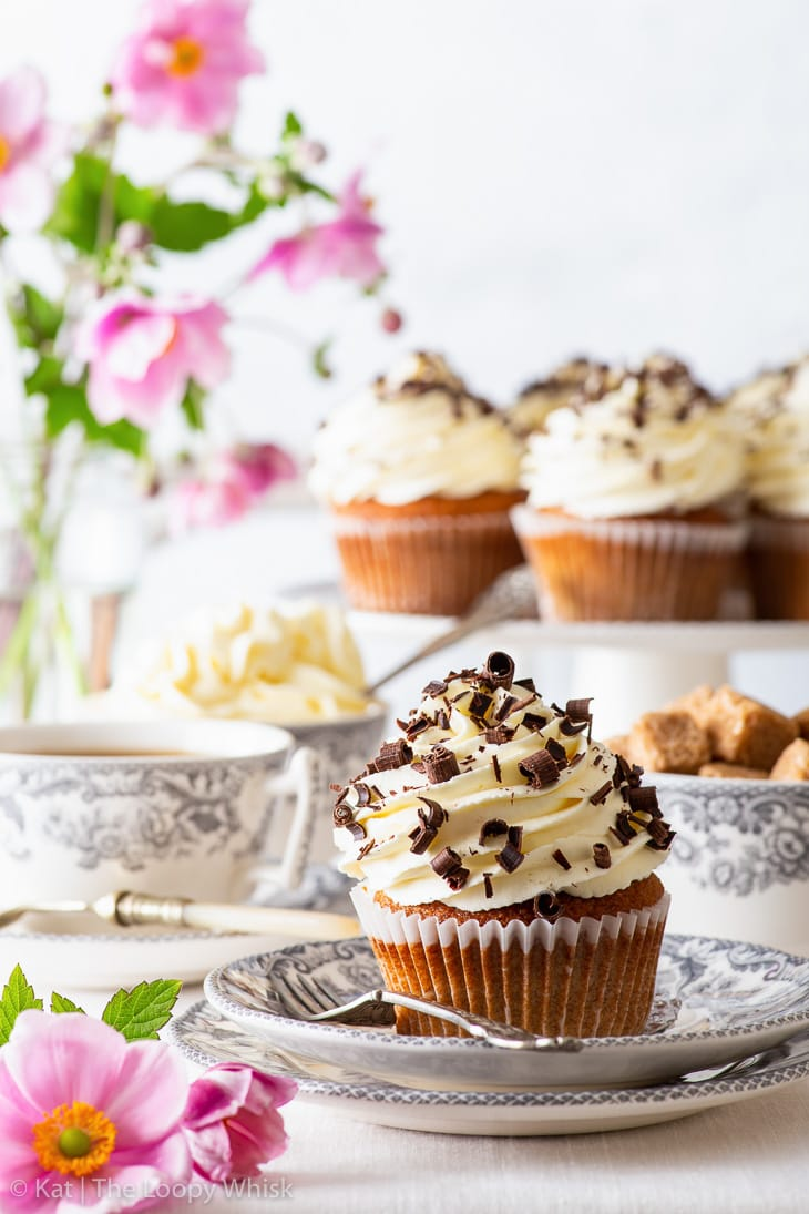 A banoffee pie cupcake on a dessert plate, with more cupcakes on a cake stand in the background.