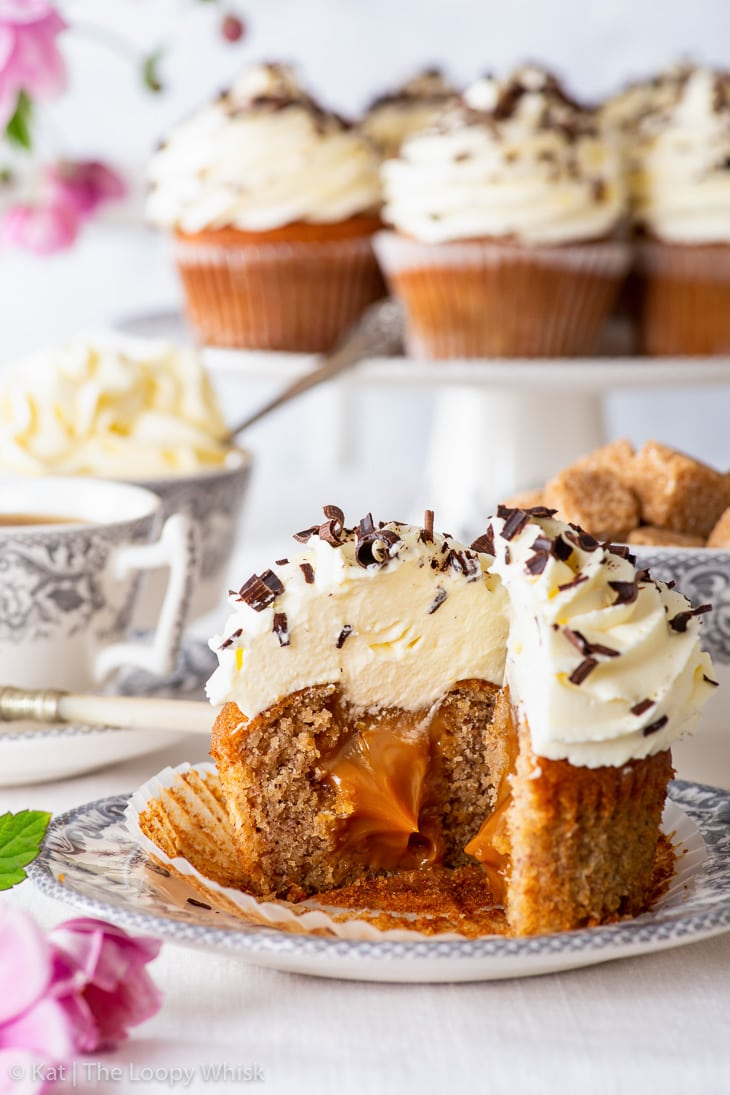 A banoffee pie cupcake on a dessert plate, with more cupcakes on a cake stand in the background. The cupcake has been cut in half, exposing the luscious caramel centre.