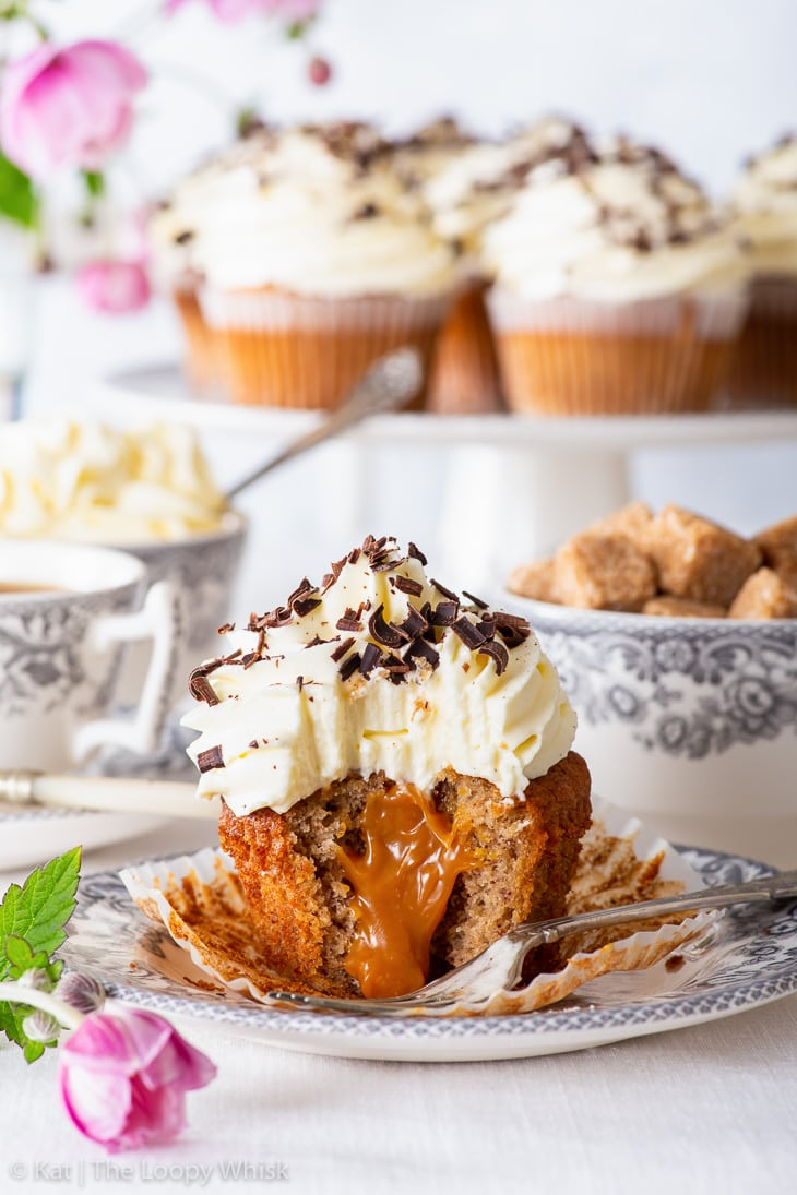 A banoffee pie cupcake on a dessert plate, with more cupcakes on a cake stand in the background. The cupcake has had a few bites taken out of it, showing its luscious caramel centre.