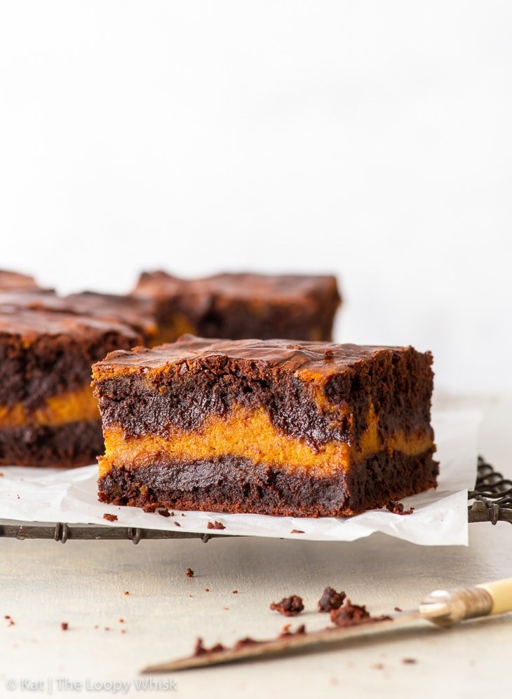 Pieces of pumpkin brownies on a wire cooling rack covered in parchment paper.