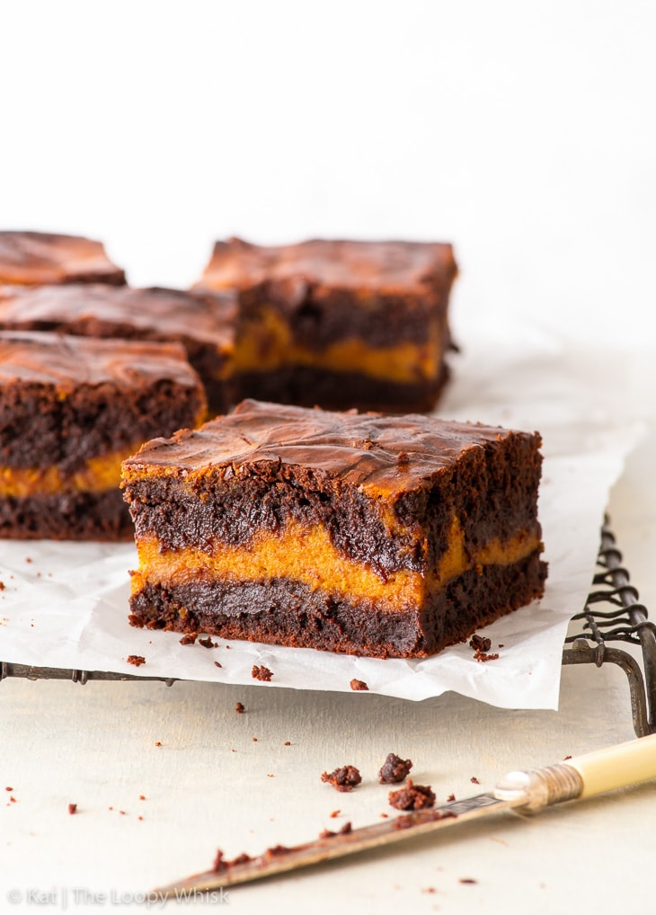 Pieces of pumpkin brownies on a wire cooling rack covered in parchment paper. A knife is in front of the cooling rack.