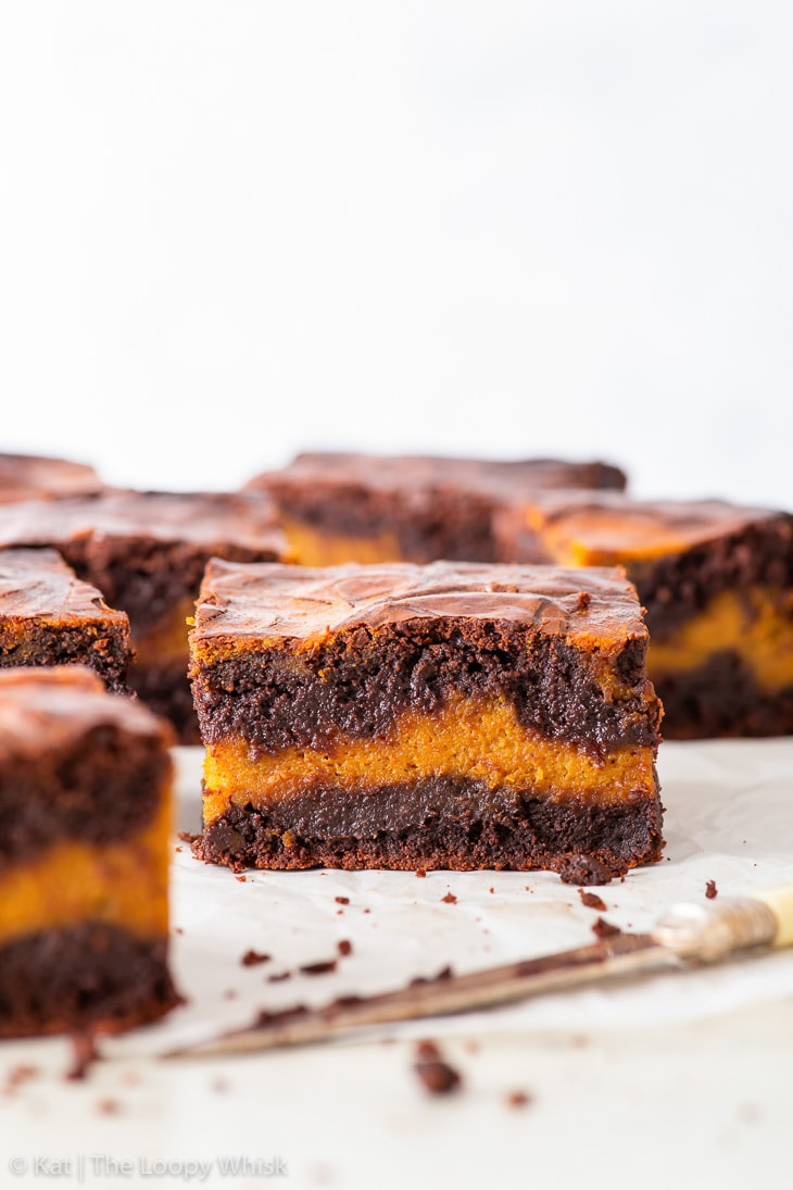 Pieces of pumpkin brownies on a piece of white parchment paper, a knife in front of them.