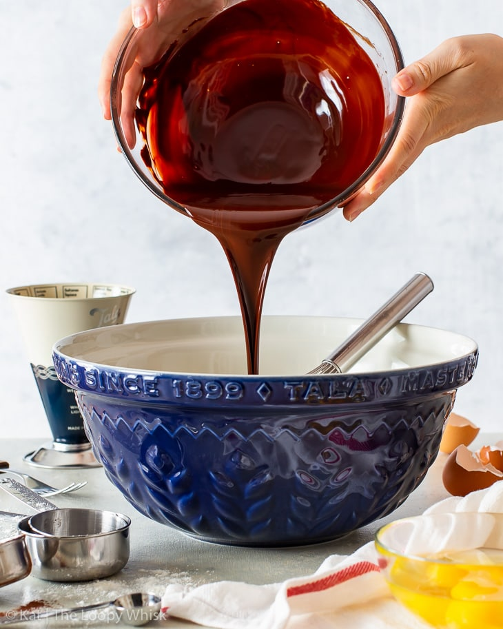 Pouring melted dark chocolate into a big blue bowl.