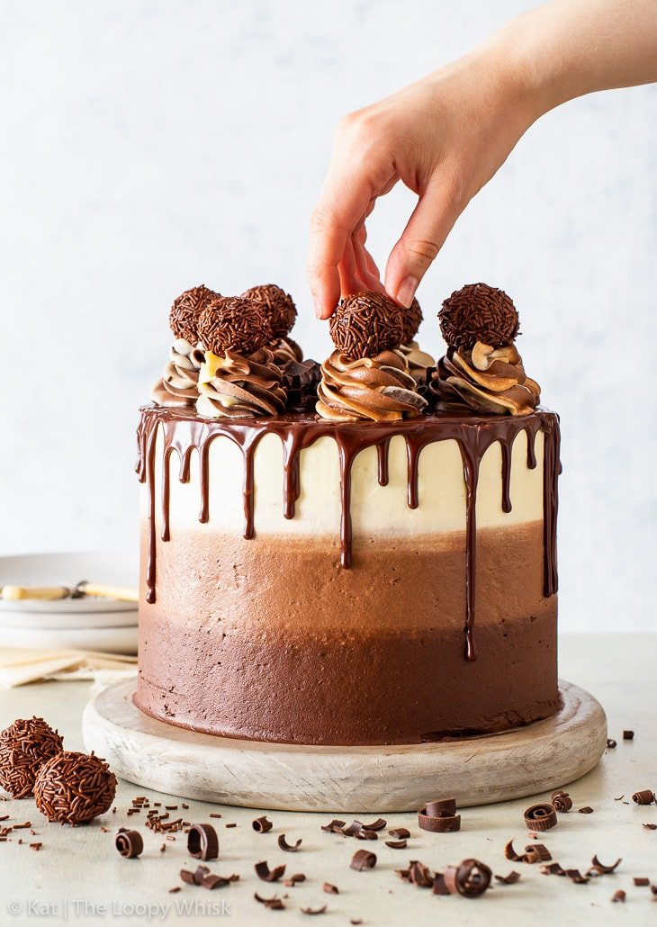 Triple chocolate cake, with ombre frosting and chocolate ganache drip, on a low wooden cake stand. A hand is holding one of the chocolate truffles on top of the cake.