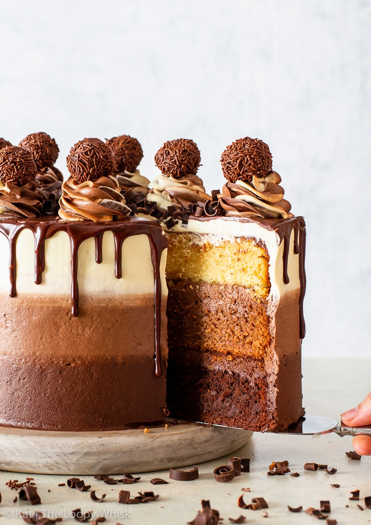 Triple chocolate cake, with ombre frosting and chocolate ganache drip, on a low wooden cake stand. A piece of the cake is being removed using a cake server.
