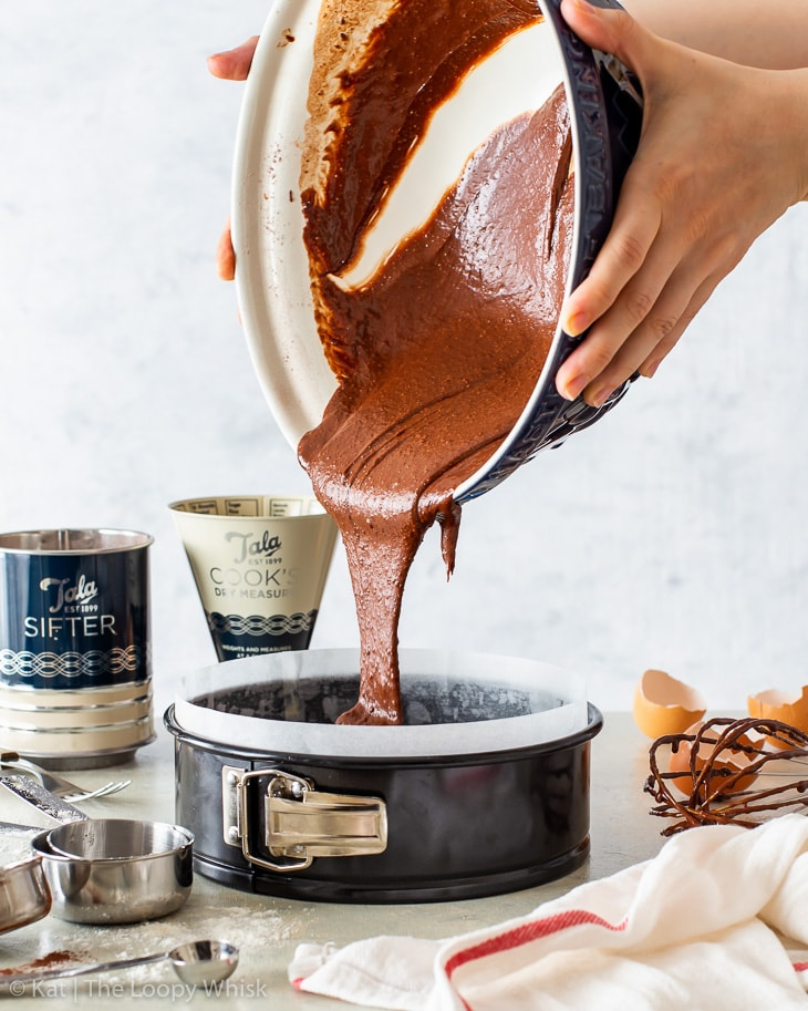 Pouring chocolate cake batter into a lined springform cake pan.