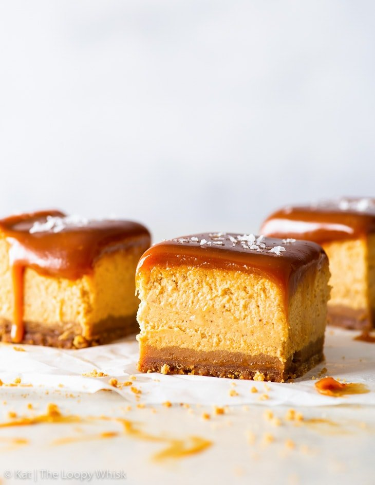 Three salted caramel pumpkin cheesecake bars on a white backdrop.