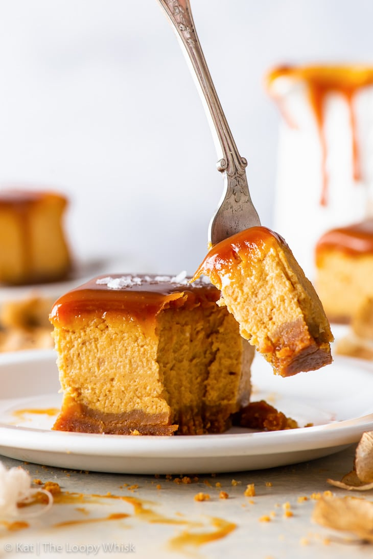 A salted caramel pumpkin cheesecake bar on a white dessert plate. A bite is being taken out of the bar with a fork. More cheesecake bars are in the background.