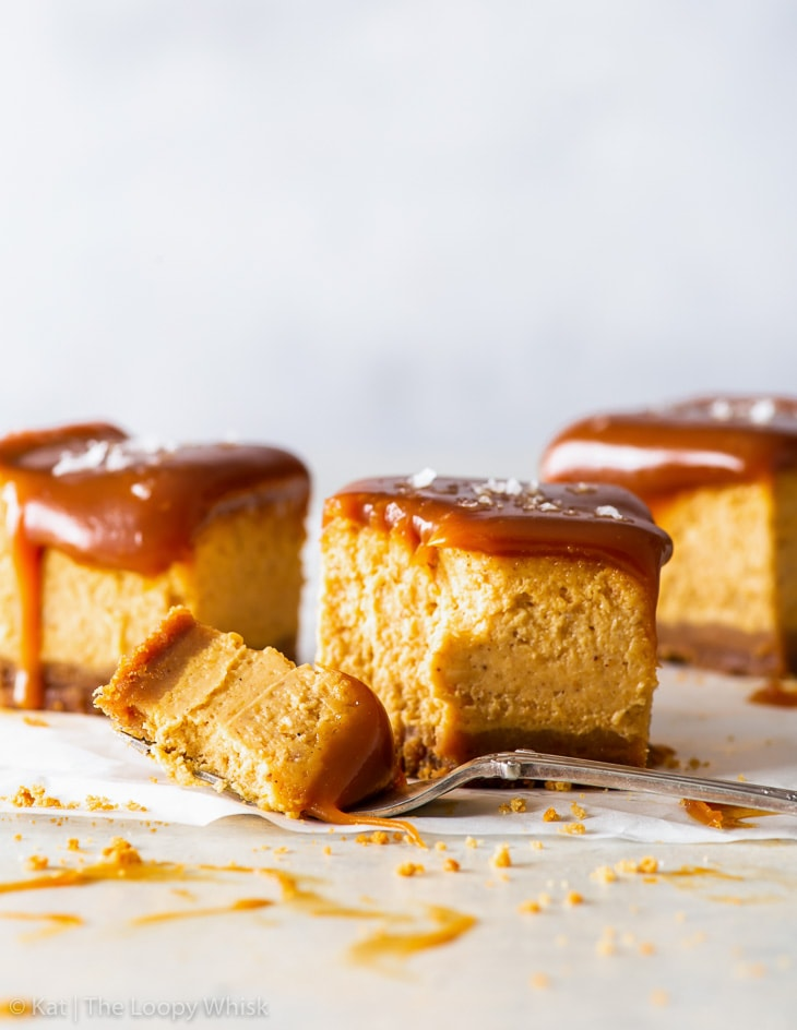 Three salted caramel pumpkin cheesecake bars on a white backdrop. A bite has been taken out of one of the bars with a fork.