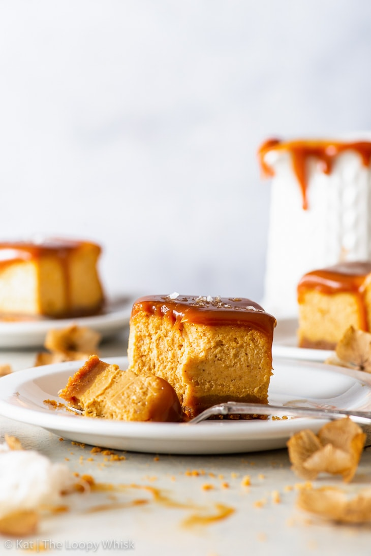 A salted caramel pumpkin cheesecake bar on a white dessert plate. A bite has been taken out of the bar with a fork. More cheesecake bars are in the background.