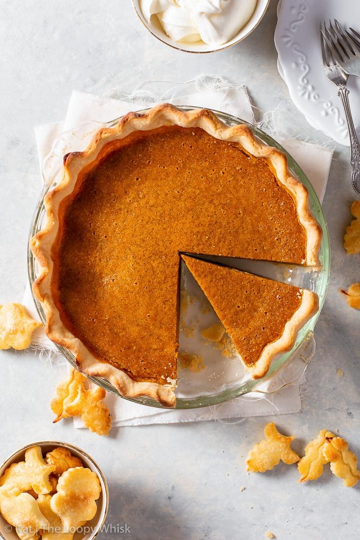 Overhead shot of gluten free pumpkin pie, with a piece cut.