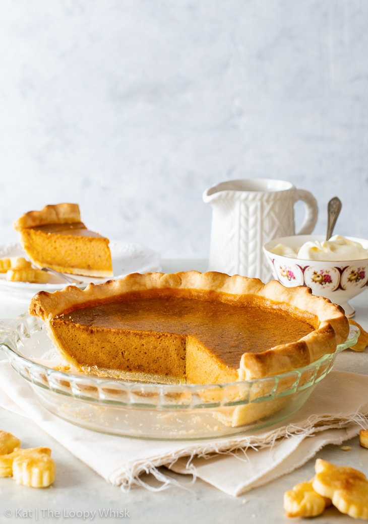 Pumpkin pie in a glass pie dish. A piece of the pie, a bowl of whipped cream and a saucer are in the background.