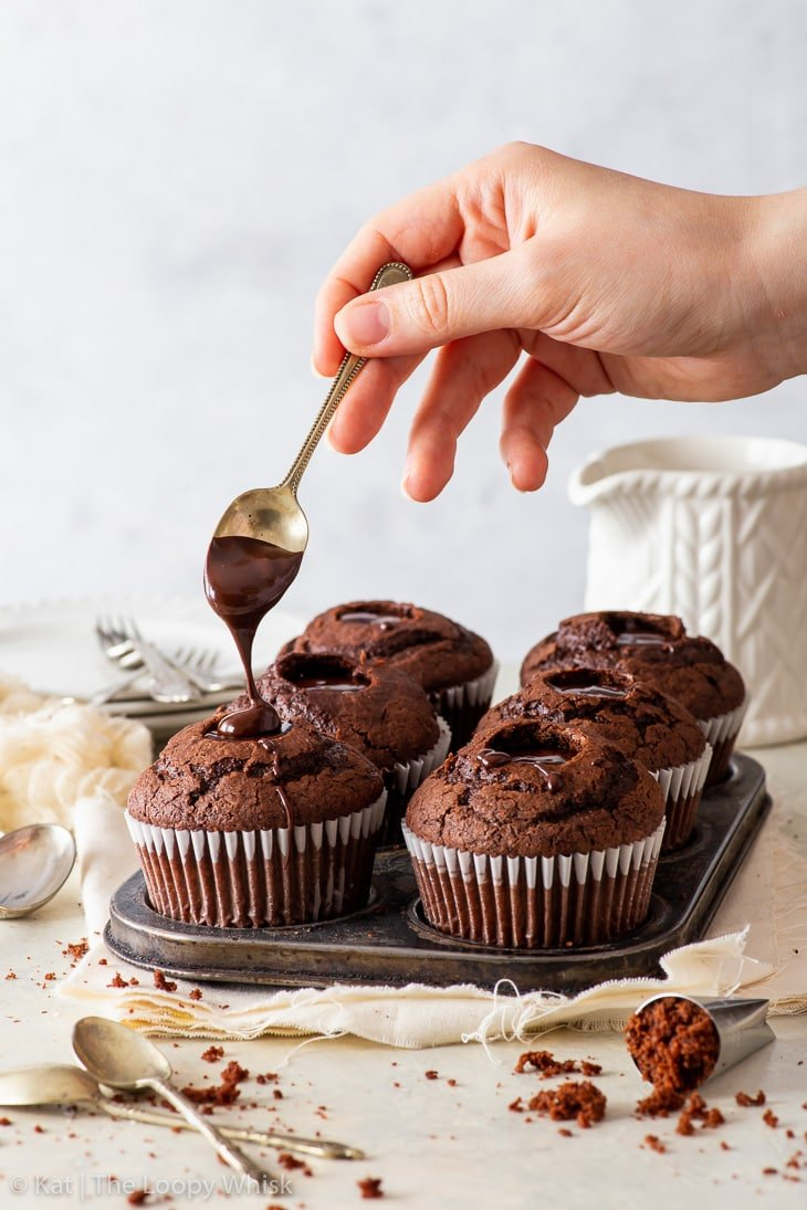 Filling cupcakes with chocolate fudge sauce.