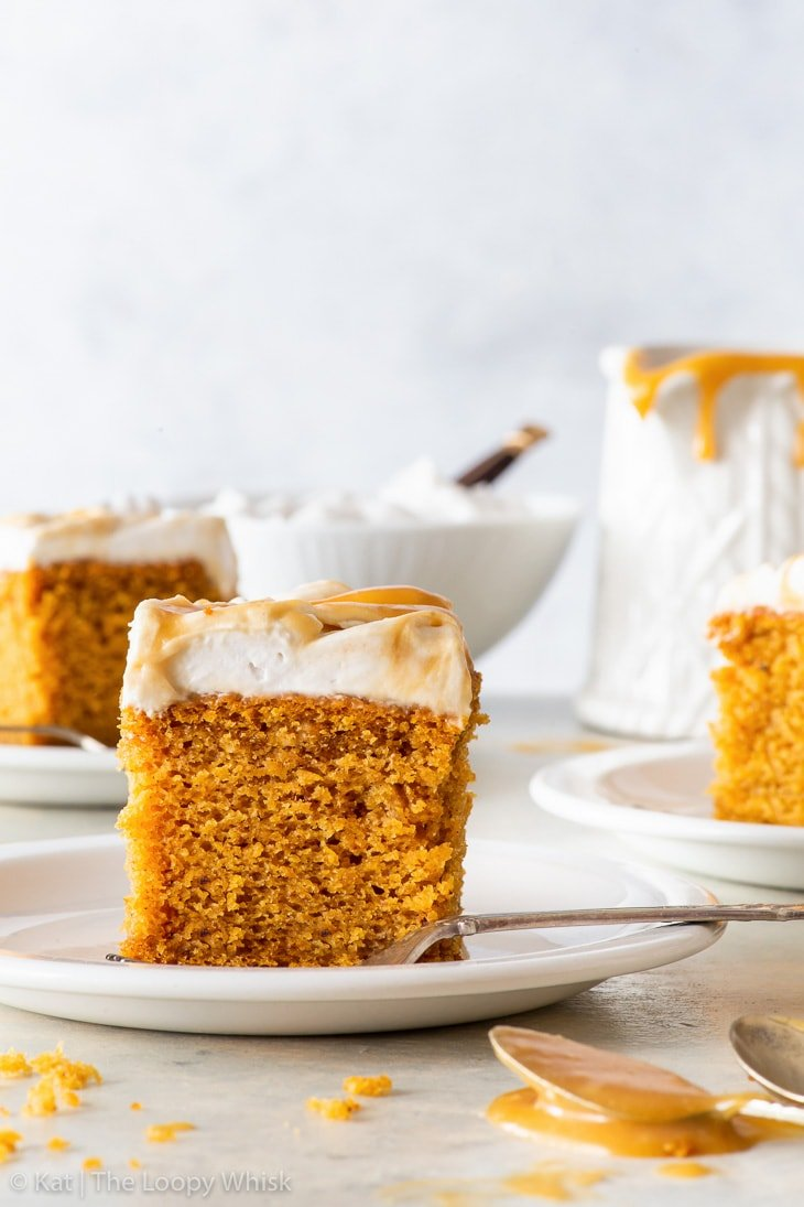 A piece of the vegan pumpkin cake on a small white plate. Two more pieces of the cake, as well as a saucer and a small bowl, are in the background.