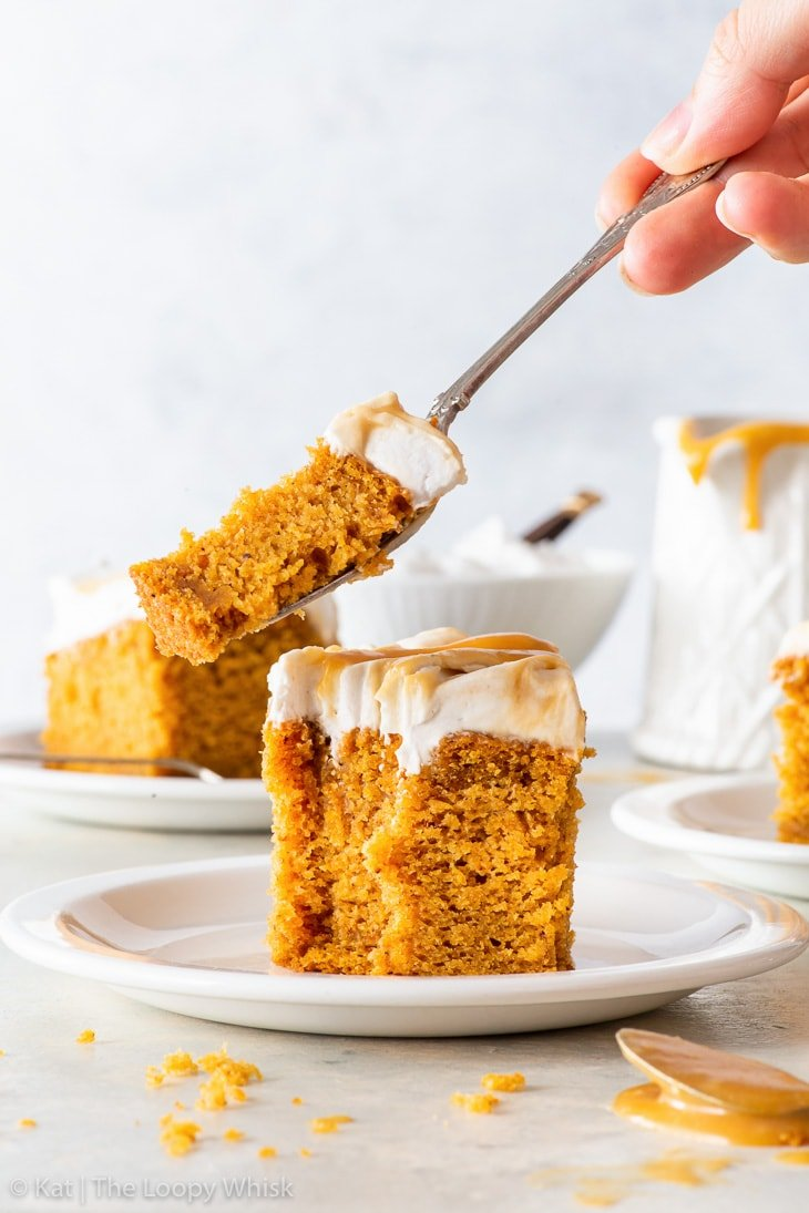 A piece of the vegan pumpkin cake on a small white plate, a bite being taken out of it.