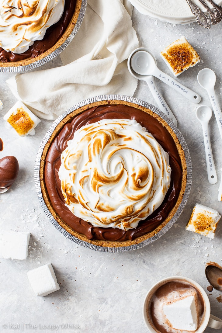 Overhead shot of a hot chocolate pie, topped with toasted Swiss meringue. Toasted marshmallows and cups of hot chocolate complete the scene.