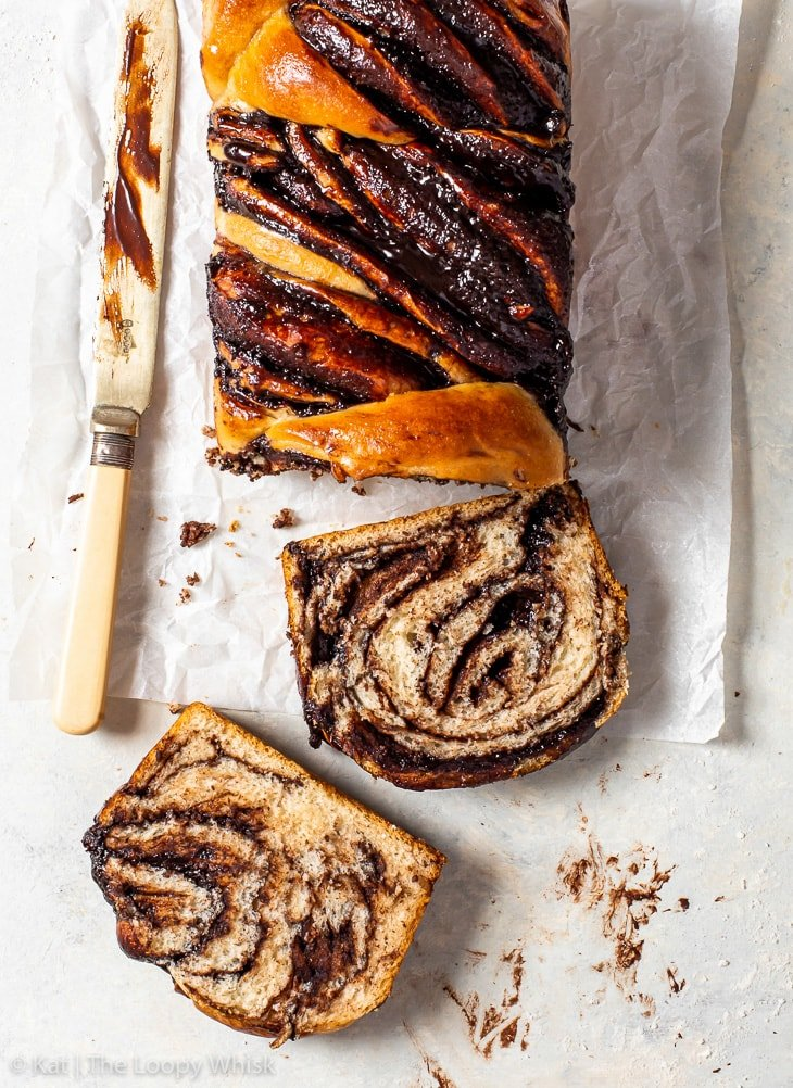 Overhead view of the vegan chocolate babka, with two pieces having been cut, on a piece of parchment paper and aa chocolate-smeared knife lying next to it.