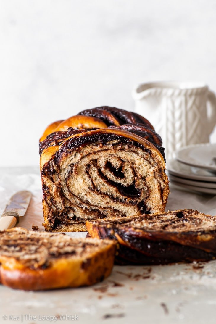 Head-on view of the vegan chocolate babka, with a few pieces having been cut. A stack of white dessert plates and a saucer are in the background.