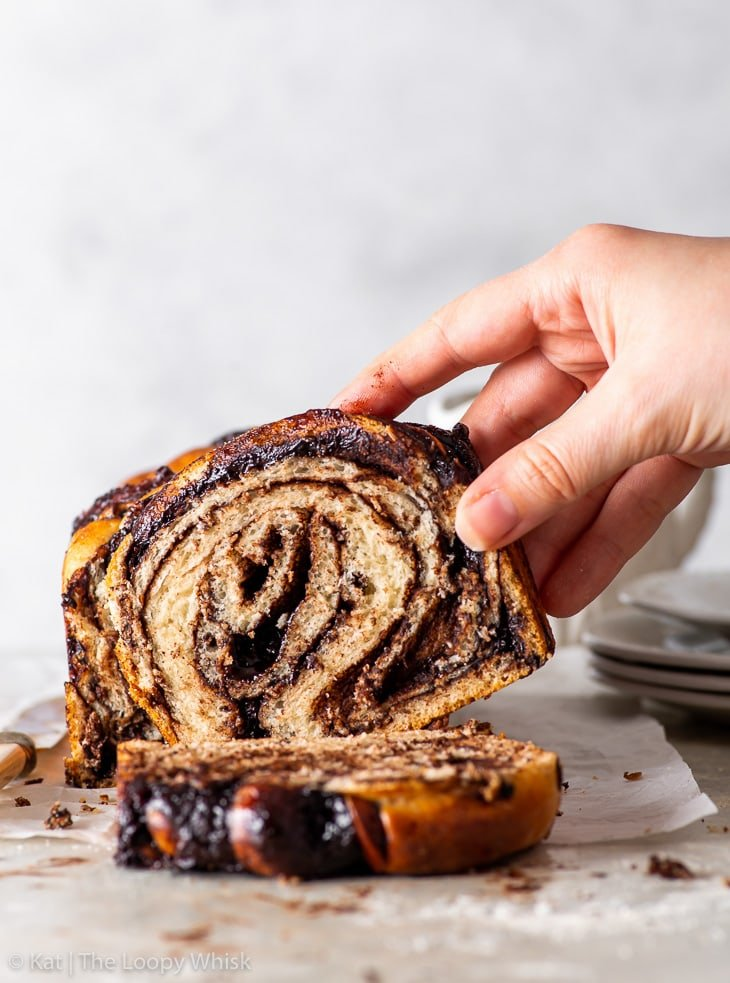 A hand holding a piece of the vegan chocolate babka.