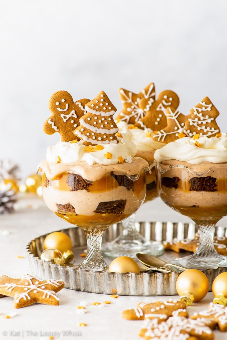 Three vegan gingerbread Christmas trifles on a metal tray, surrounded by gold Christmas baubles.