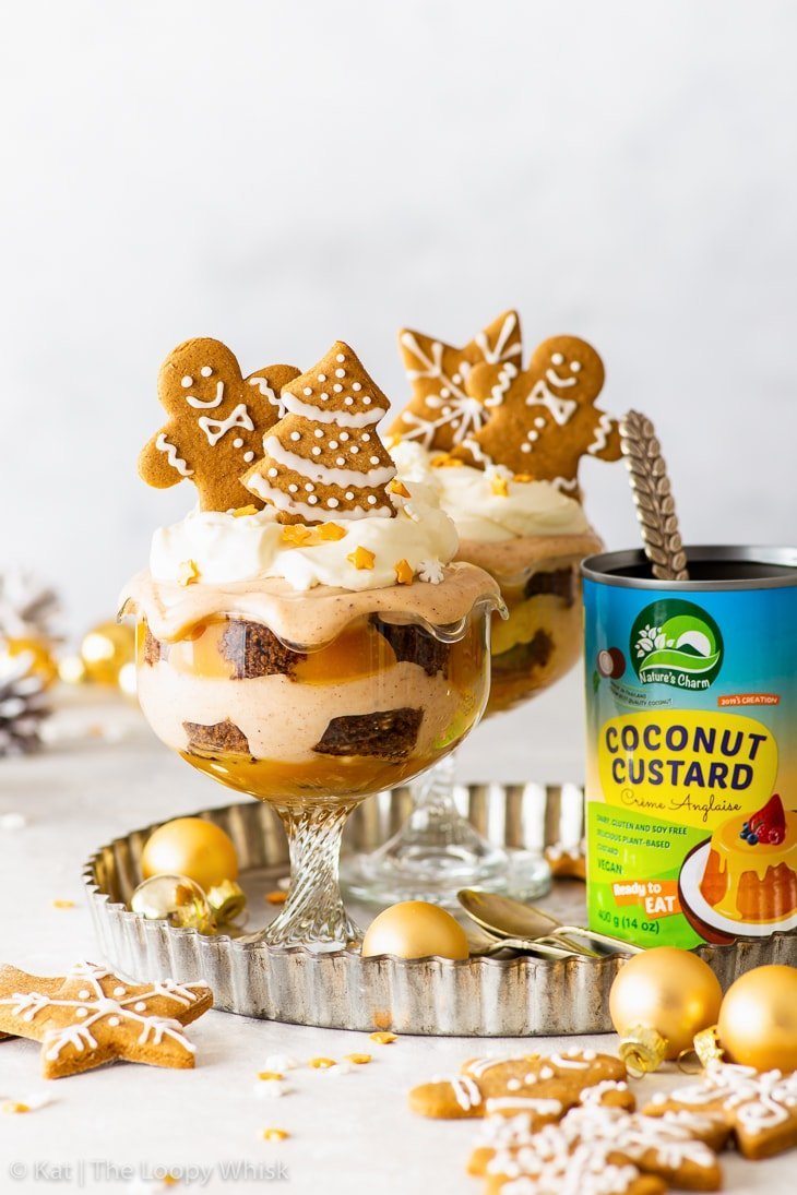 Two vegan gingerbread Christmas trifles on a metal tray, surrounded by gold Christmas baubles.