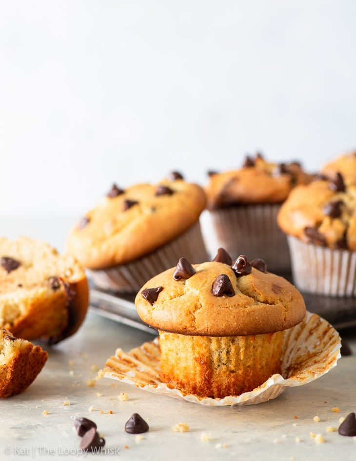 Gluten free chocolate chip muffin, with the wrapper unwrapped. More muffins in a metal tin are in the background.