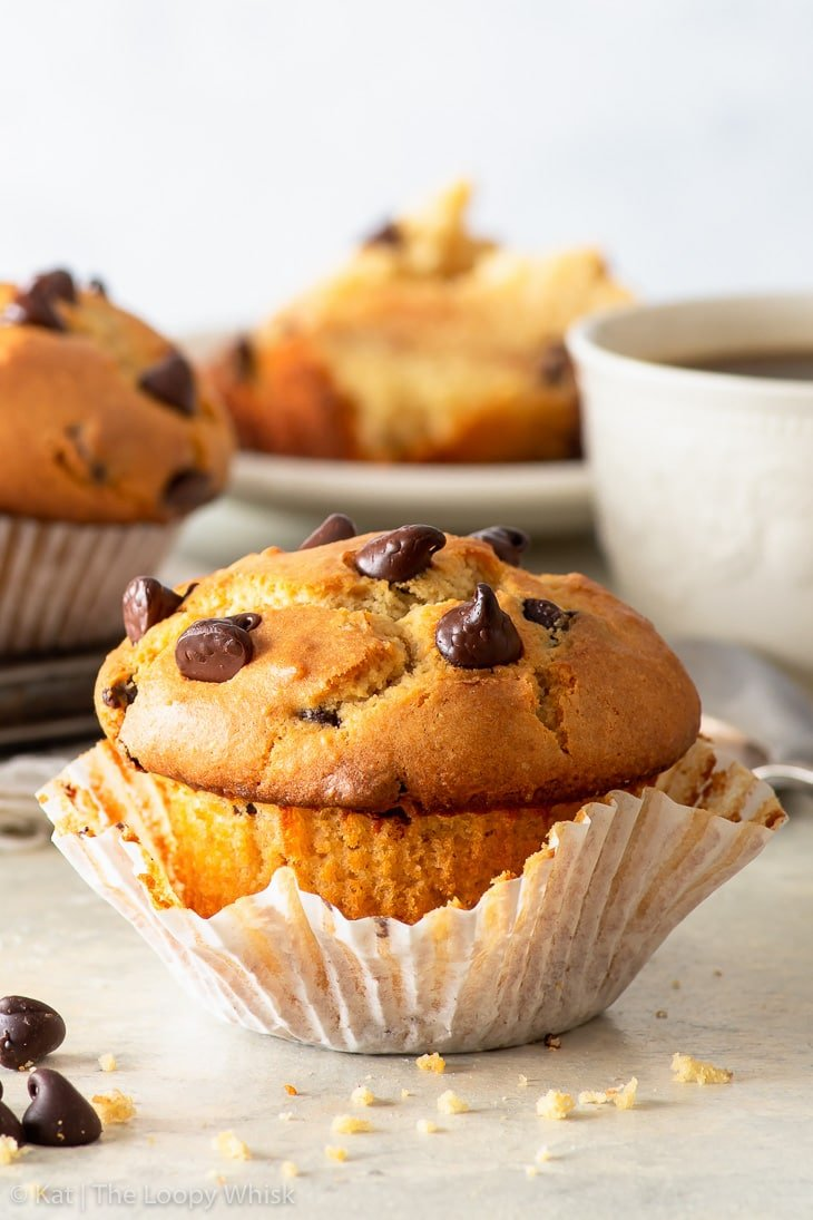 Gluten free chocolate chip muffin, with the wrapper partially unwrapped. A cup of coffee and more muffins are in the background.