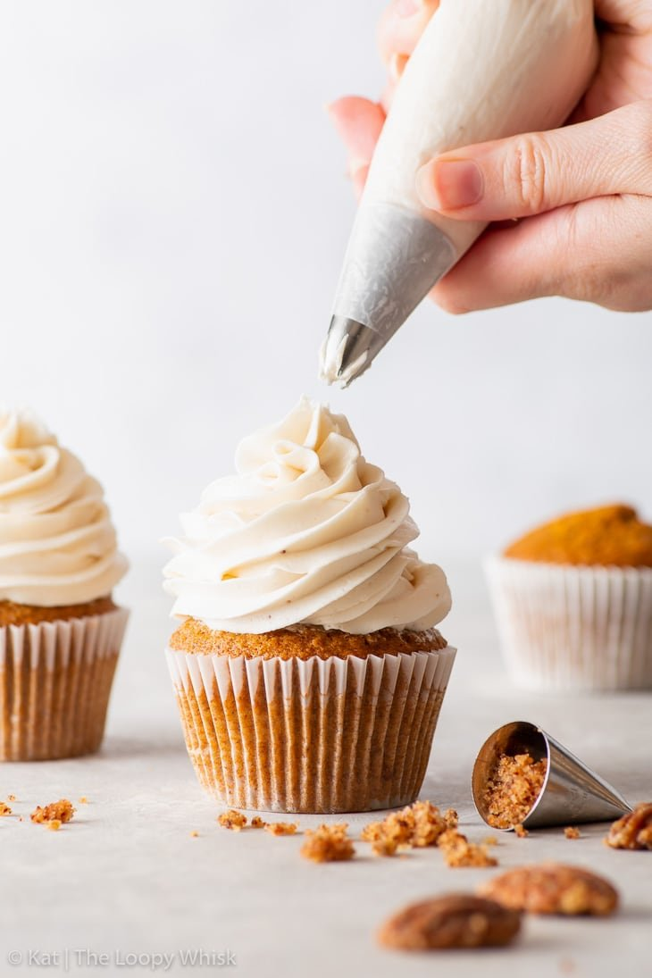 Piping vegan maple buttercream frosting on top of pecan cupcakes.