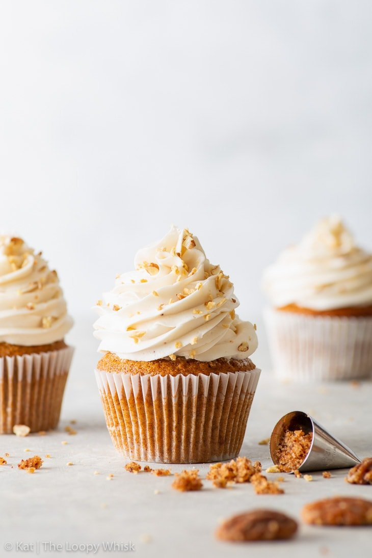 Three vegan maple & pecan cupcakes on a brigth background.