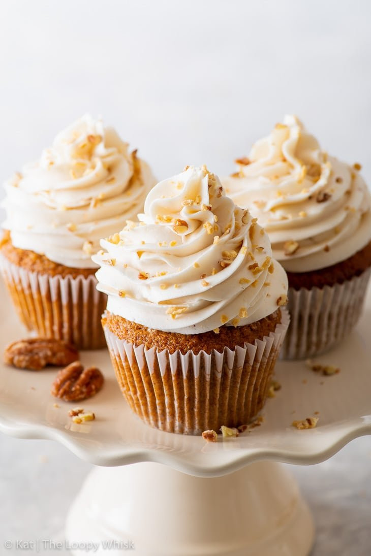 Close-up of vegan maple & pecan cupcakes on a white cake stand.