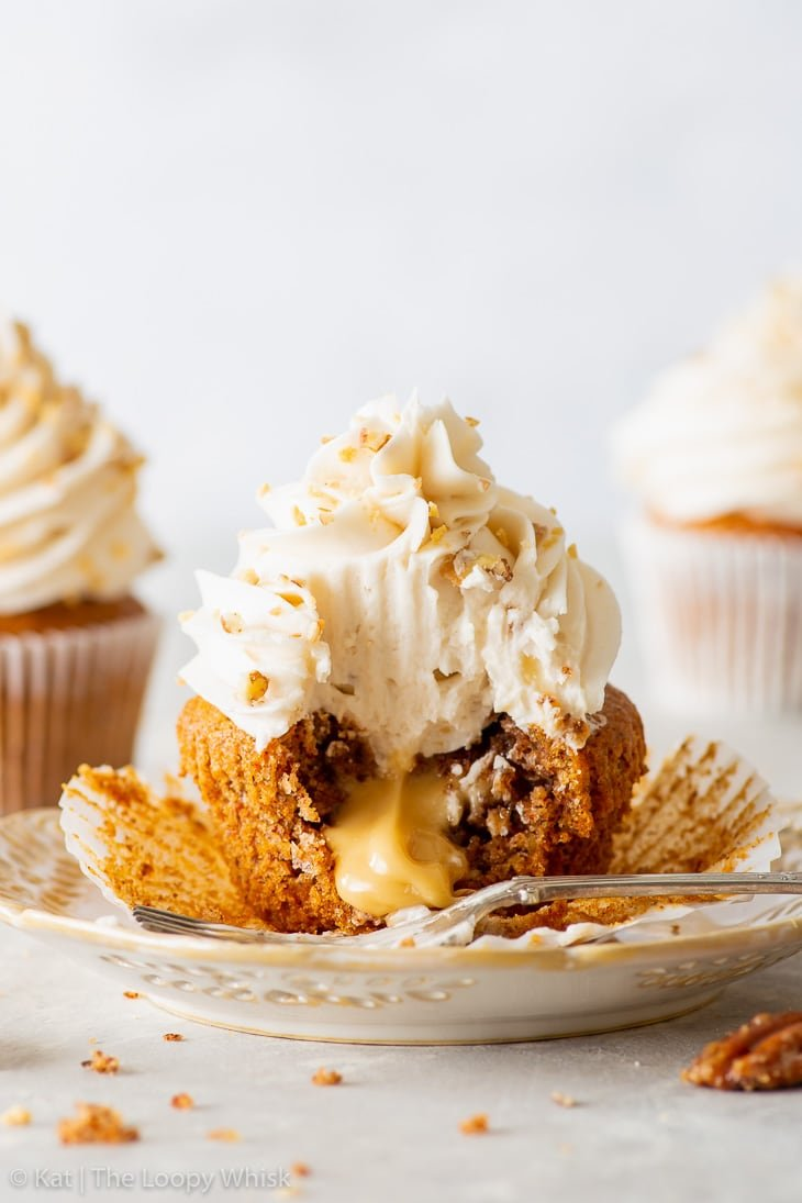 Vegan maple & pecan cupcake on a white dessert plate. A bite has been taken out of it, and the maple spread is luxuriously oozing out of the middle.