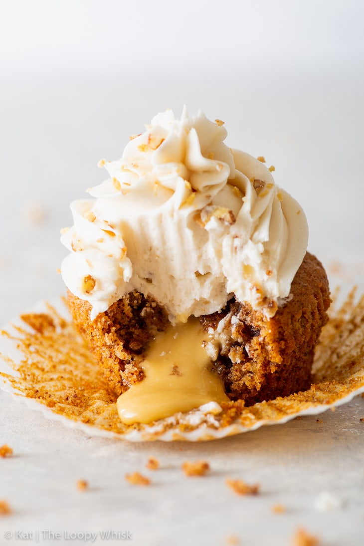 Close-up of a vegan maple & pecan cupcake. A bite has been taken out of it, and the maple spread is luxuriously oozing out of the middle.